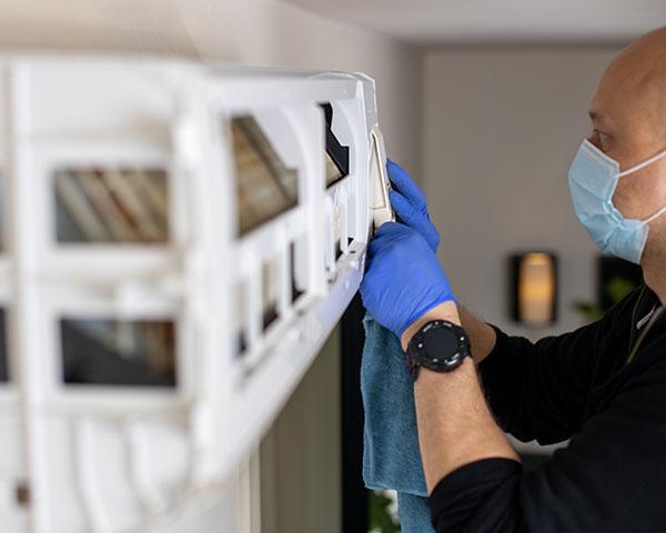 Mann fra Power Clean demonterer en varmepumpe for å utføre rens