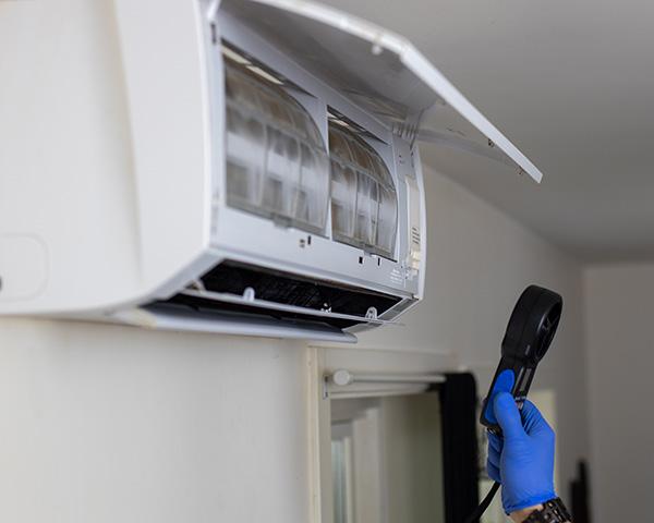 Mann fra Power Clean utfører kontrollmåling av en varmepumpe etter rens