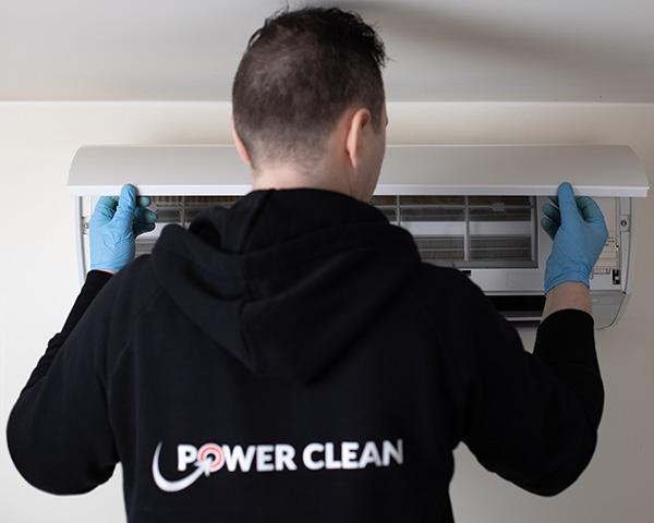 Mann fra Power Clean monterer og ferdigstiller en varmepumpe etter rens